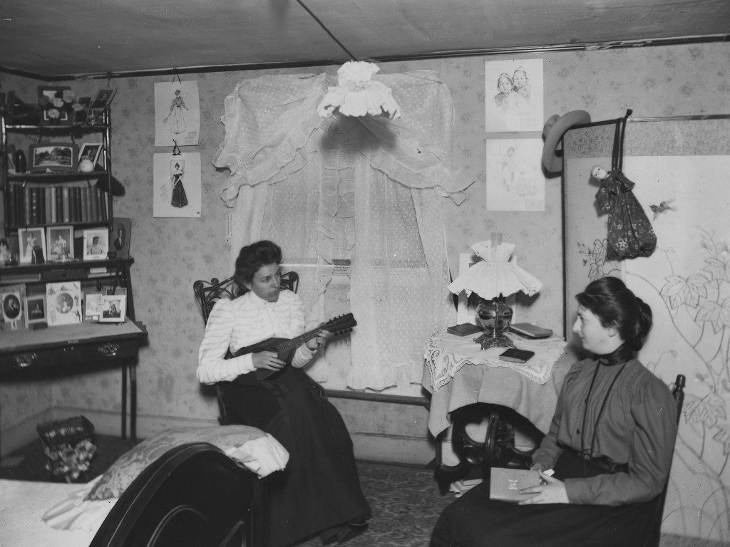 Student entertaining another in a Boarding House dorm room